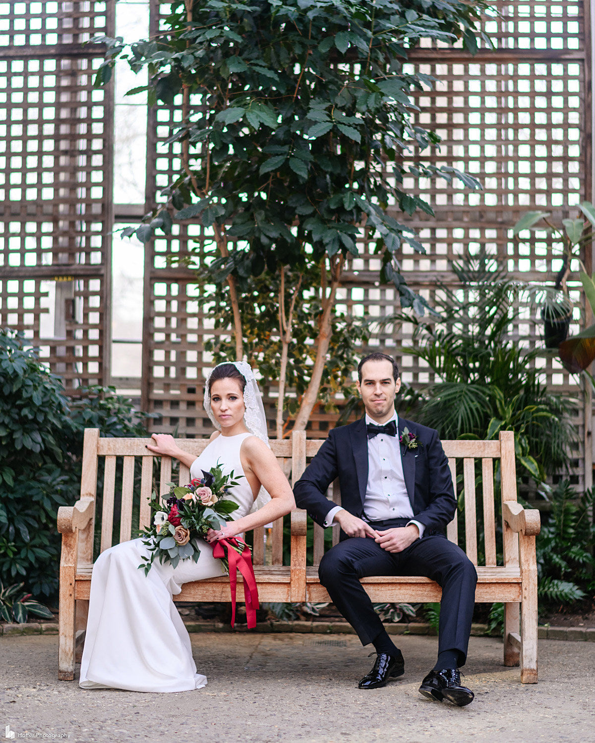 Bride and groom sit on a bench at the Horticulture Center in Philadelphia
